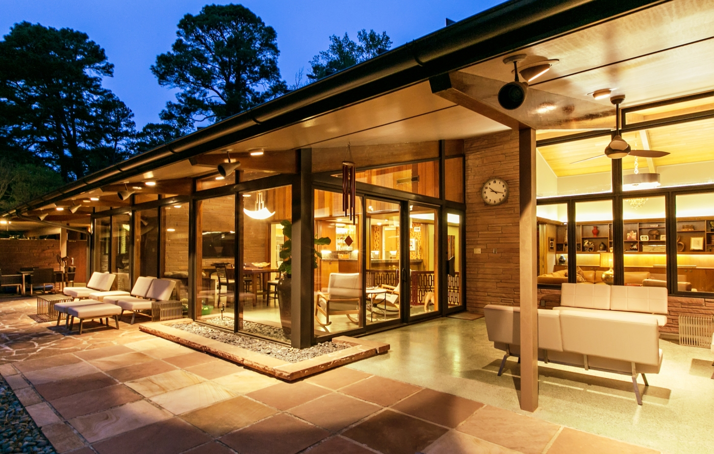 Rear exterior of mid century modern house with large Marvin windows and doors