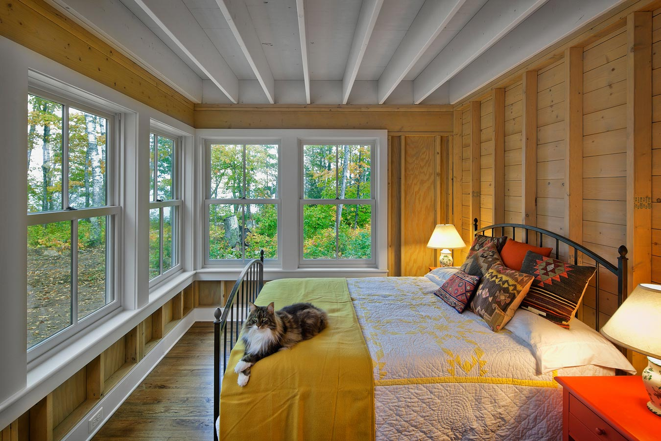 Bedroom with natural wood walls and large Marvin Double Hung windows, with a cozy bedspread and a cute little cat.