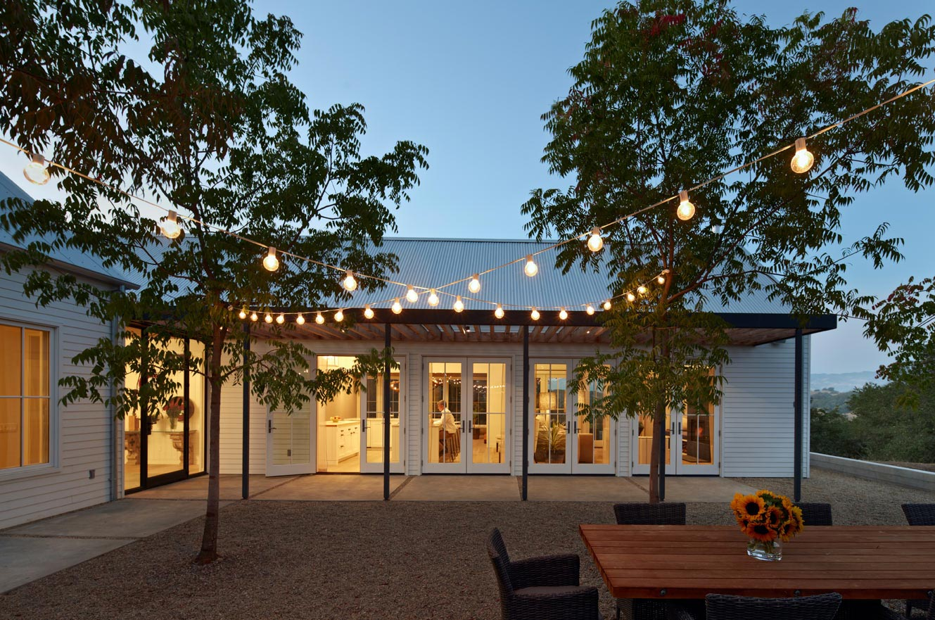 View into a home from an outdoor living space with cafe lights, looking in on large swinging patio doors.